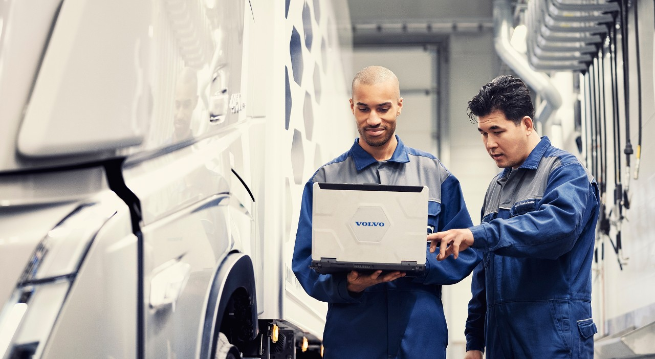 Zwei Volvo Servicetechniker stehen neben einem Lkw und schauen auf einen Laptop