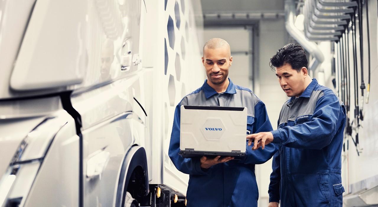 Deux techniciens de service Volvo regardent un ordinateur portable tout en se tenant à côté d'un véhicule